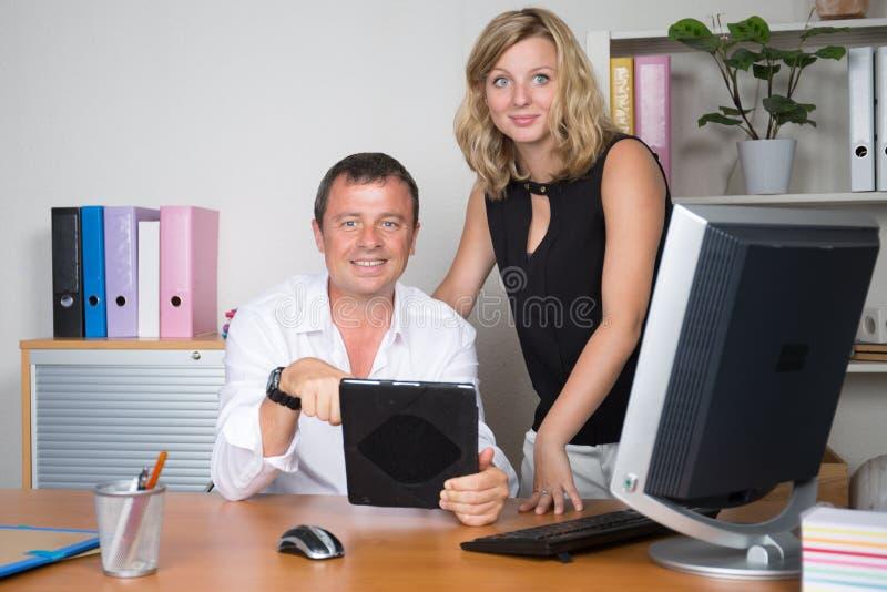 Bedrijfsmensen die pret hebben en op werkplaatskantoor babbelen met computer en tablet royalty-vrije stock foto's