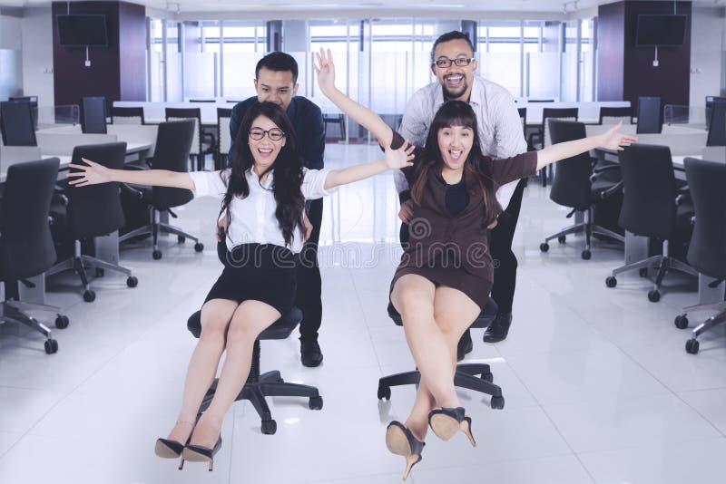 Bedrijfsmensen die pret hebben die op bureaustoelen rennen royalty-vrije stock afbeelding