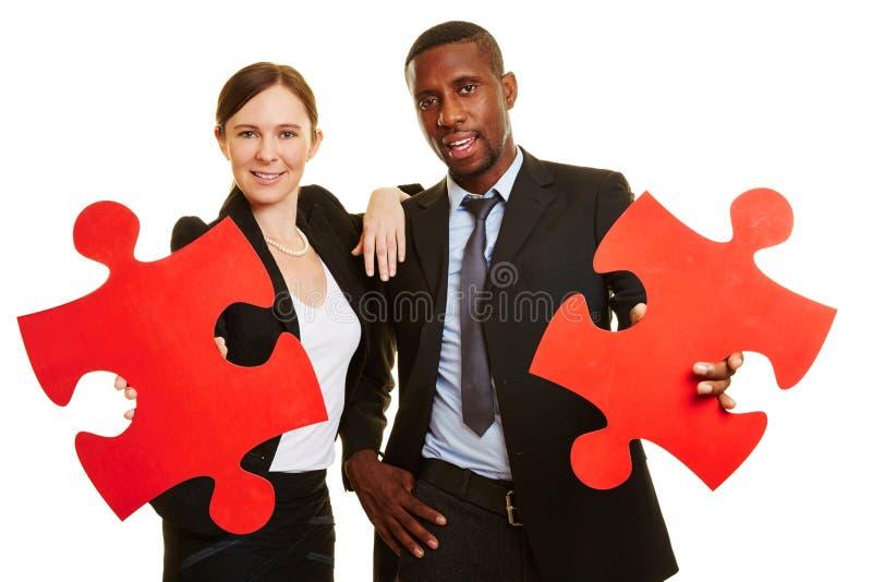 Bedrijfsmensen die rode puzzelstukken houden stock fotografie