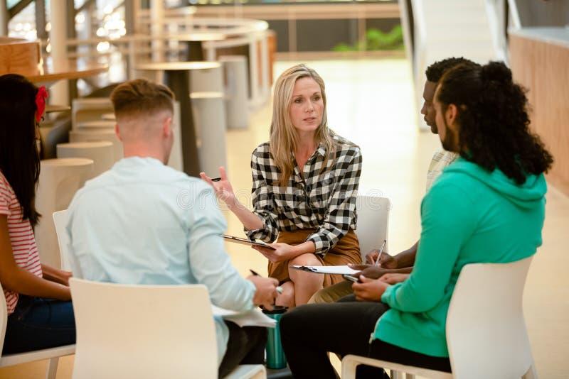 Bedrijfsmensen die samen en een groepsbespreking in een modern bureau zitten hebben stock foto