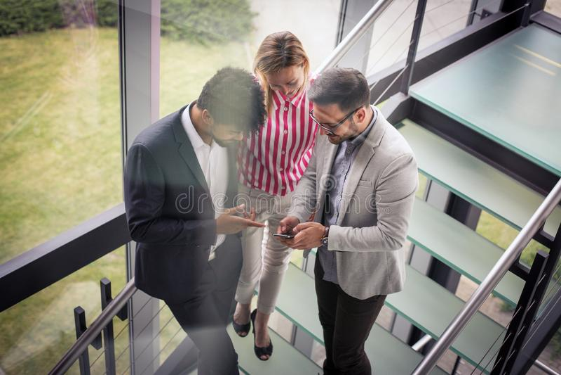 Bedrijfsmensen die slimme telefoon in de bouw van bureau met behulp van Zaken royalty-vrije stock foto's