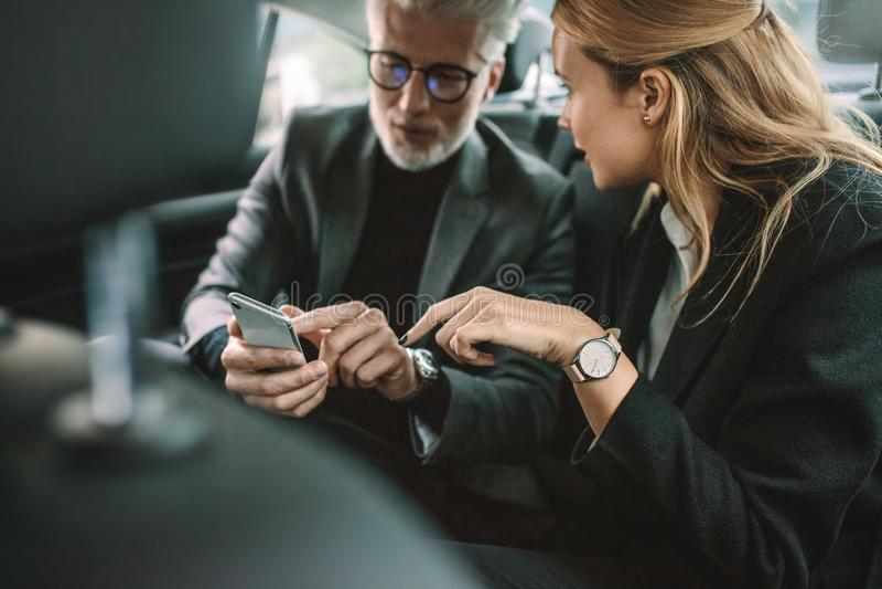 Bedrijfsmensen die slimme telefoon in taxi met behulp van stock afbeelding