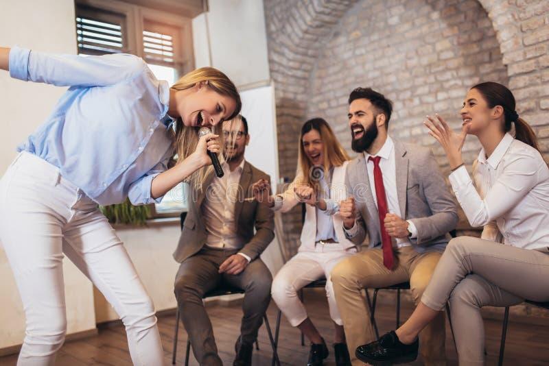 Bedrijfsmensen die team opleidingsoefening maken tijdens team de bouwseminarie het zingen karaoke stock foto's