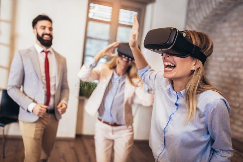 Bedrijfsmensen die team opleidingsoefening maken tijdens team de bouwseminarie die VR-glazen gebruiken stock foto