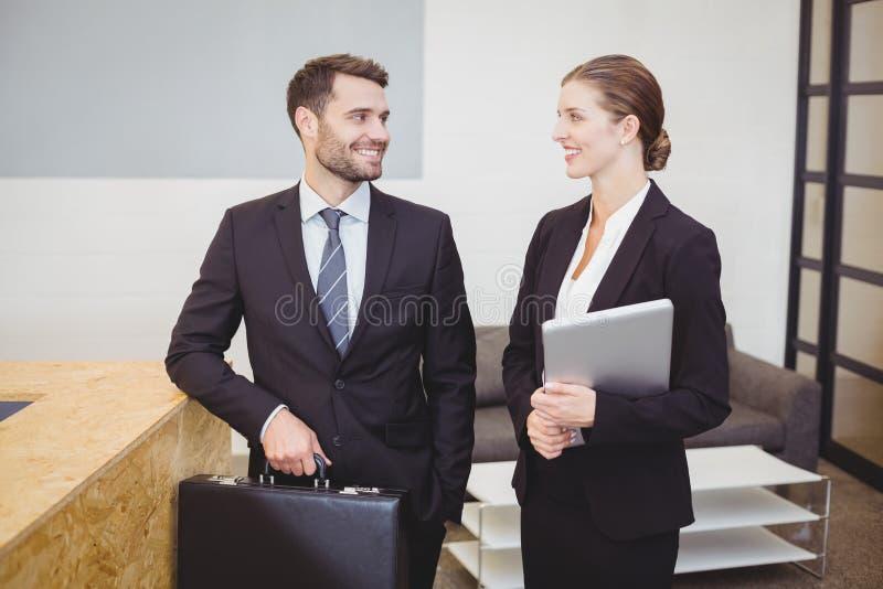 Bedrijfsmensen die terwijl het spreken in bureau glimlachen royalty-vrije stock foto's