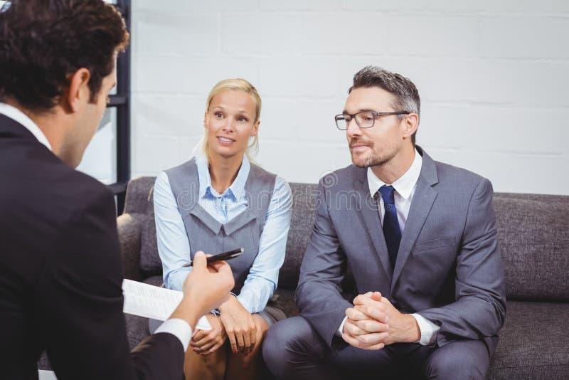 Bedrijfsmensen die terwijl het zitten op bank bespreken stock fotografie