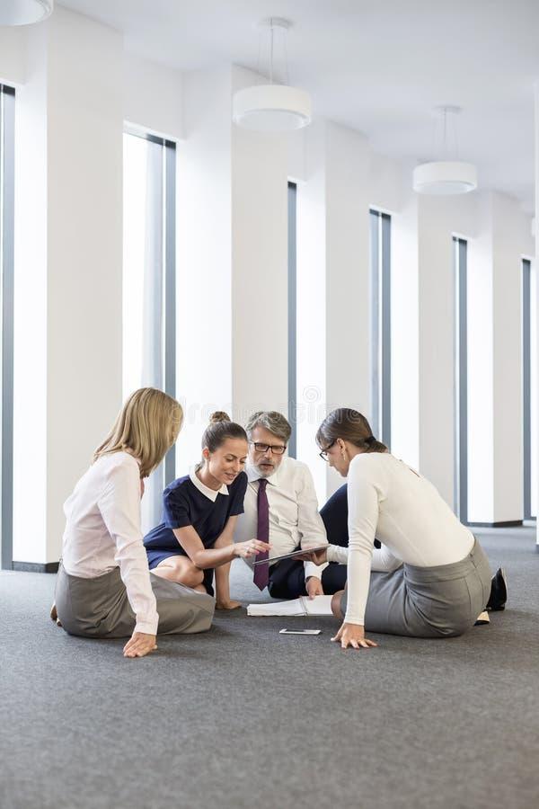Bedrijfsmensen die terwijl het zitten op vloer op kantoor bespreken stock fotografie