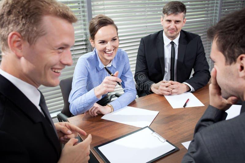 Bedrijfsmensen die tijdens commerciële vergadering lachen stock afbeeldingen