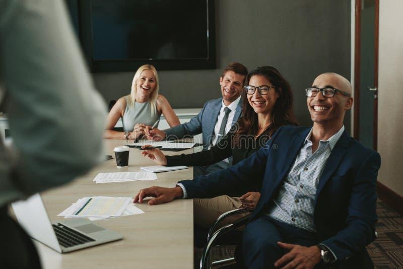 Bedrijfsmensen die tijdens vergadering in raadsruimte glimlachen stock afbeeldingen