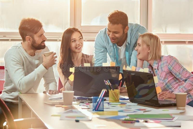 Bedrijfsmensen die in toevallige doek samen terwijl het bekijken laptop in bureau glimlachen stock afbeeldingen