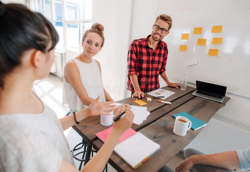 Bedrijfsmensen die in vergaderzaal op creatief kantoor bespreken royalty-vrije stock afbeeldingen