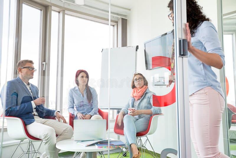 Bedrijfsmensen die vrouwelijke collega status in schuifdeur bekijken royalty-vrije stock afbeelding