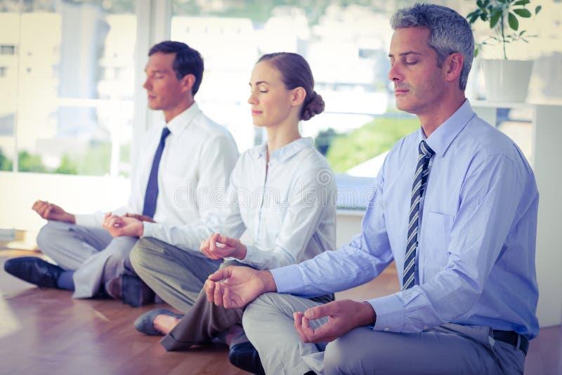 Bedrijfsmensen die yoga op vloer doen royalty-vrije stock afbeeldingen