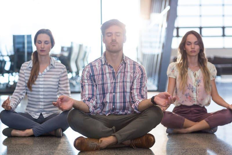 Bedrijfsmensen die yoga op vloer uitvoeren royalty-vrije stock foto