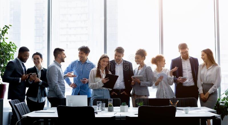 Bedrijfsmensen die zich tegen venster bevinden, die het werk bespreken stock afbeelding