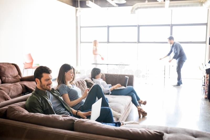 Bedrijfsmensen die in zitkamerruimte ontspannen stock afbeelding