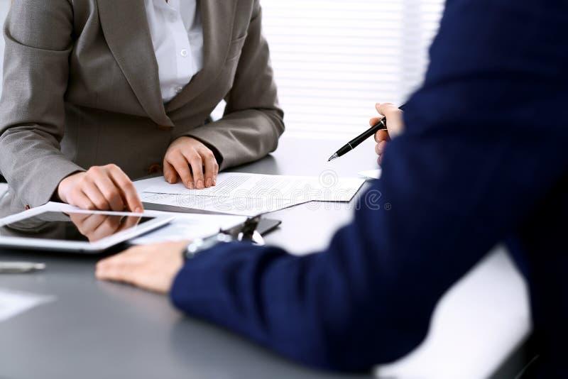 Bedrijfsmensen en advocaat die contractdocumenten bespreken die bij de lijst, handenclose-up zitten Groepswerk of groepsverrichti royalty-vrije stock foto's