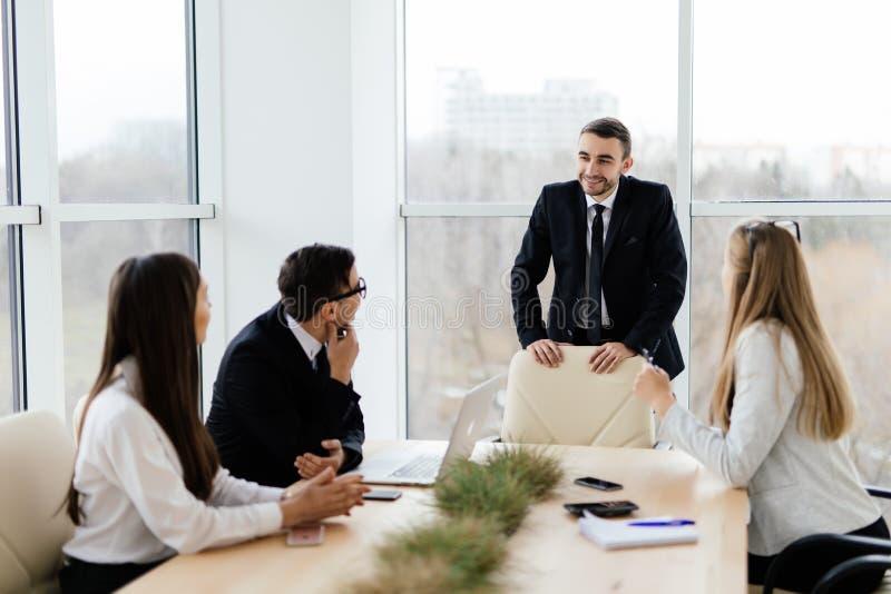 Bedrijfsmensen in het formalwear bespreken met leider iets terwijl het zitten samen bij de lijst stock foto's