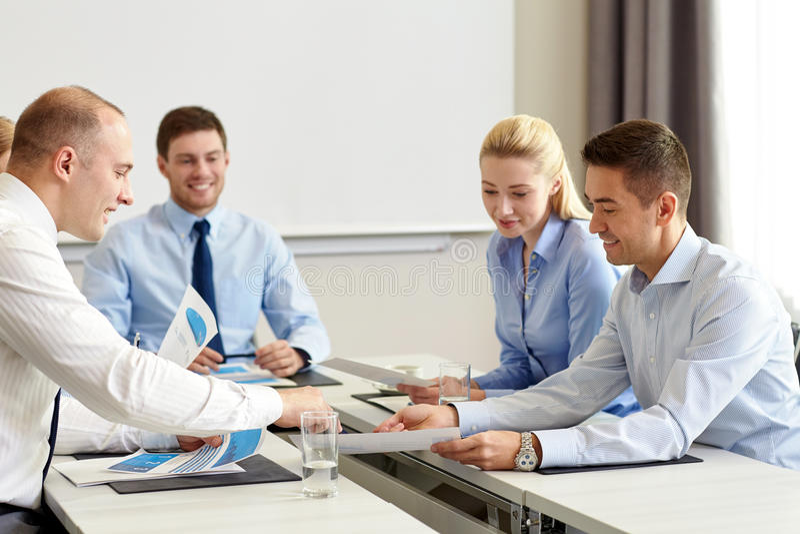 Bedrijfsmensen met documenten die in bureau samenkomen stock afbeelding
