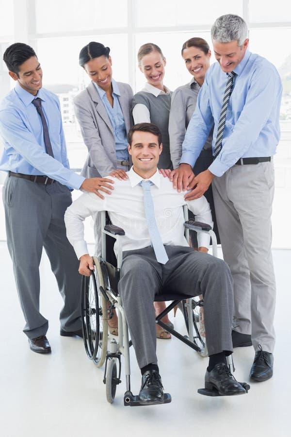 Bedrijfsmensen ondersteunend hun collega in rolstoel royalty-vrije stock foto's