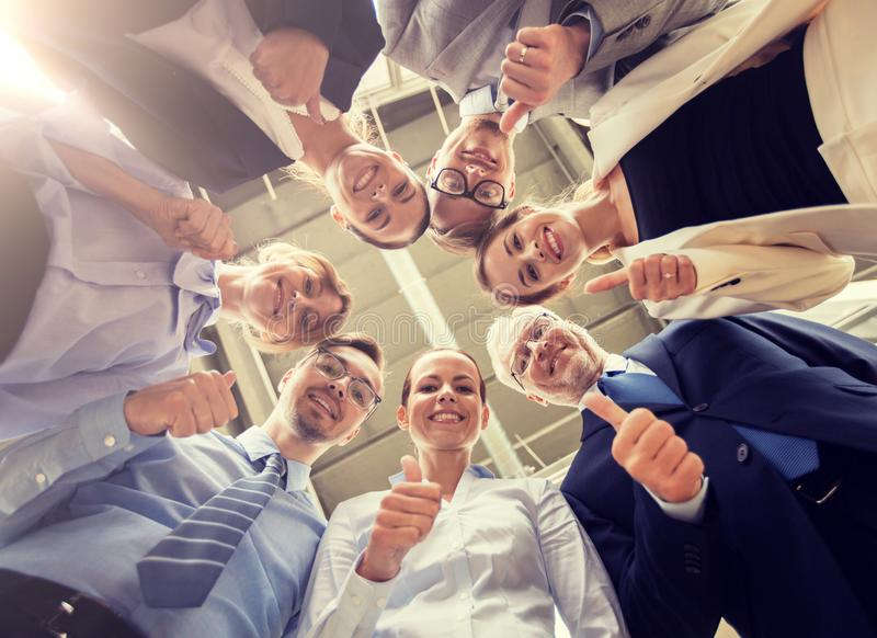 Bedrijfsmensen sneeuwende duimen omhoog op kantoor stock fotografie