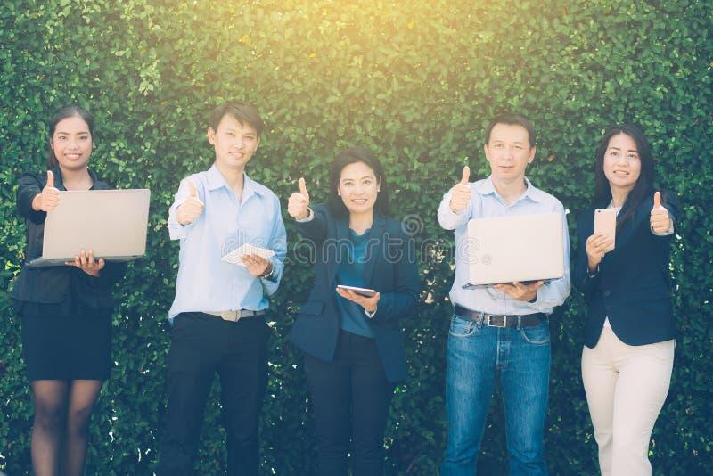 Bedrijfsmensengebaar groot met het Ontmoeten van het Collectieve Digitale Concept van de Apparatenverbinding op boommuur stock foto