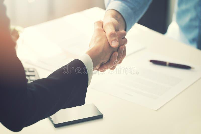 Bedrijfsmensenhanddruk na vennootschapcontract het ondertekenen stock foto
