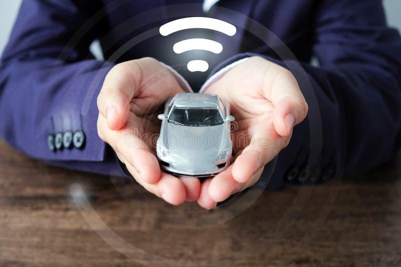 Bedrijfsmensenhanden die auto en wifipictogram, slim autoconcept houden stock foto's