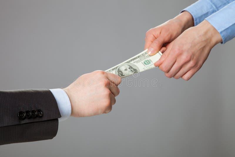 Bedrijfsmensenhanden die geld trekken stock afbeelding