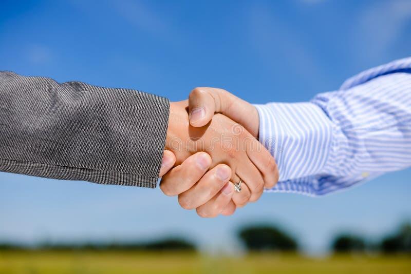 Bedrijfsmensenhandenschudden op blauwe hemel in openlucht royalty-vrije stock afbeelding