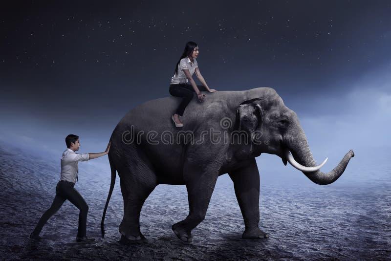 Bedrijfsmensenhulp het duwen olifant terwijl zijn vriend op het zit stock foto's