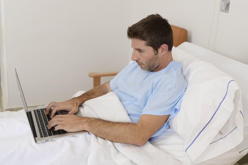 Bedrijfsmensenintern als patiënt in ziekenhuis die aan ziekte lijden en bij het kliniekbed het werken met laptop royalty-vrije stock afbeelding