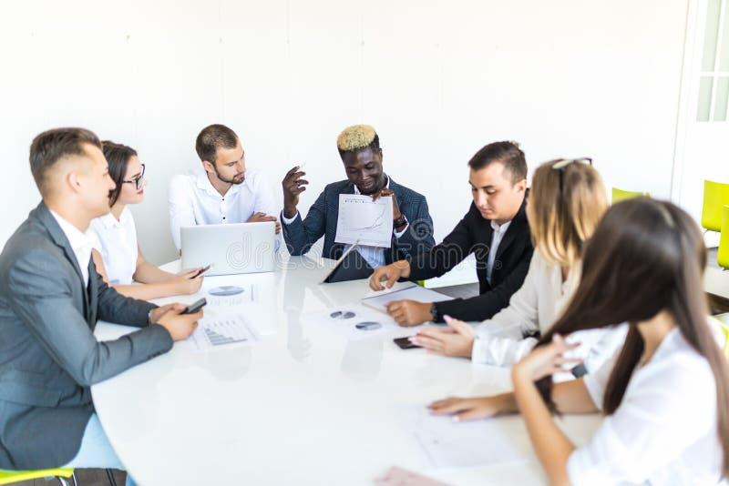 Bedrijfsmensenteam bij vergaderings werkdocumenten samen in bureau Het definitieve project komt samen stock afbeelding
