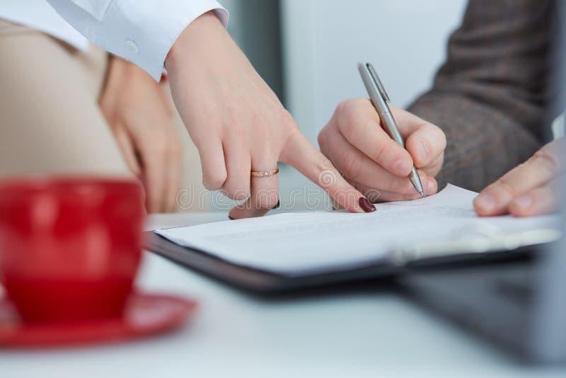 Bedrijfsmensenzitting bij bureau en het ondertekenen van een contract stock afbeelding