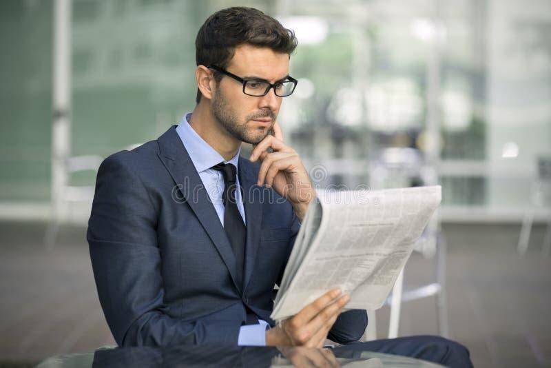 Bedrijfsmensenzitting bij koffiewinkel met een krant stock afbeelding