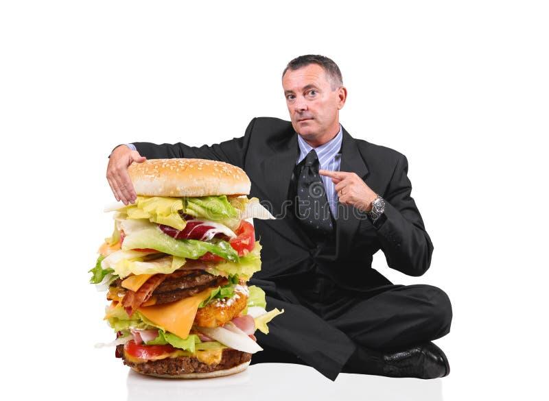 Bedrijfsmensenzitting dichtbij een grote sandwich op witte achtergrond royalty-vrije stock foto