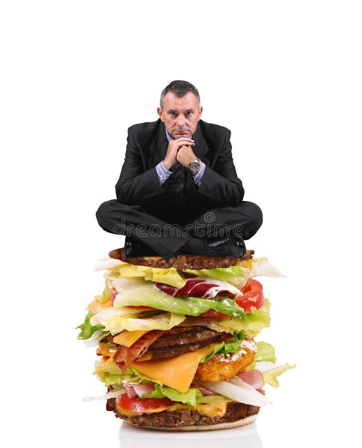 Bedrijfsmensenzitting op een grote sandwich op witte achtergrond royalty-vrije stock afbeelding