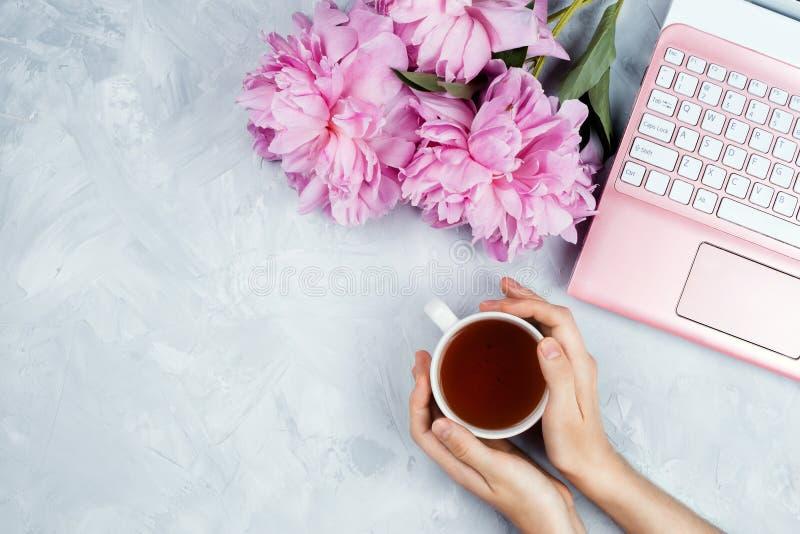 Bedrijfsmodel met roze laptop, pioenenboeket en vrouwen` s handen die kop van warme thee houden royalty-vrije stock fotografie