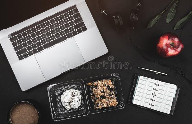 Bedrijfsonderbreking met zoete koekjes en verse appel Laptop, hoofdtelefoons en notaboek royalty-vrije stock foto