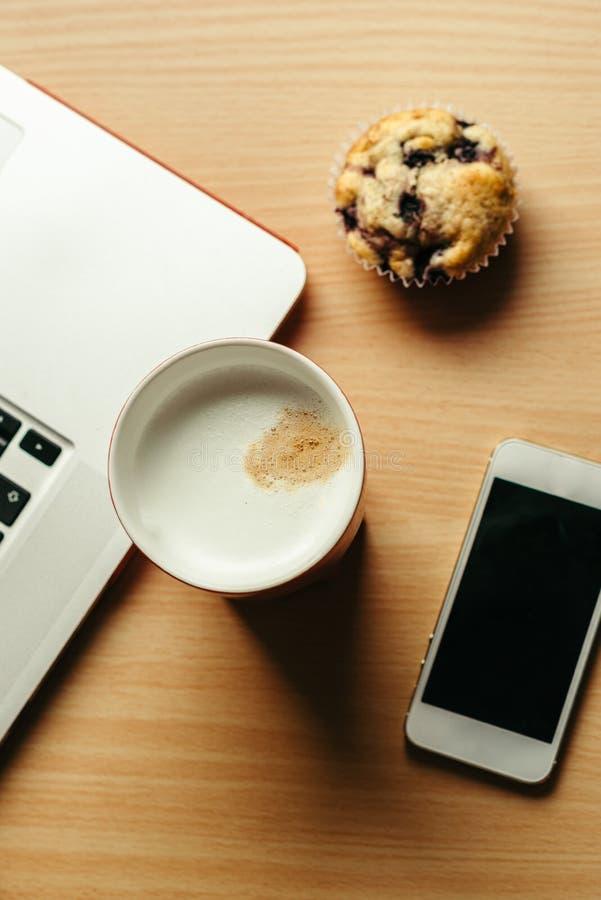 Bedrijfsontbijt met koffie, muffin, laptop en cellphone royalty-vrije stock foto's