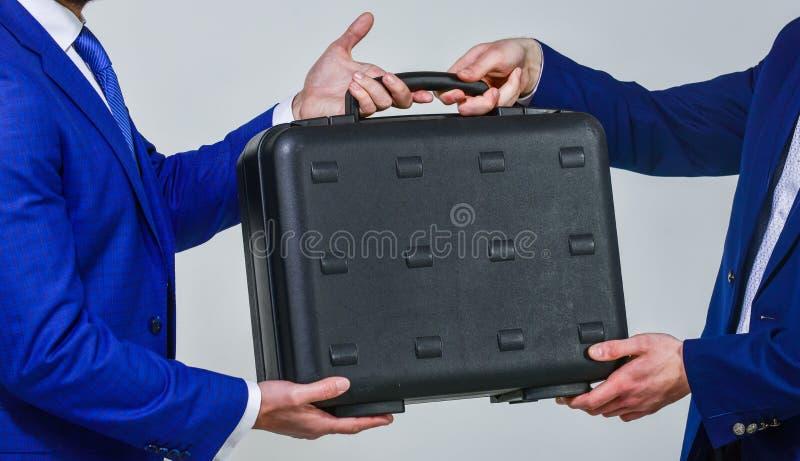 Bedrijfsoverdrachtconcept De mannelijke aktentas van de handgreep Overdracht van geval in handen van partners Overdracht van onwe royalty-vrije stock afbeeldingen