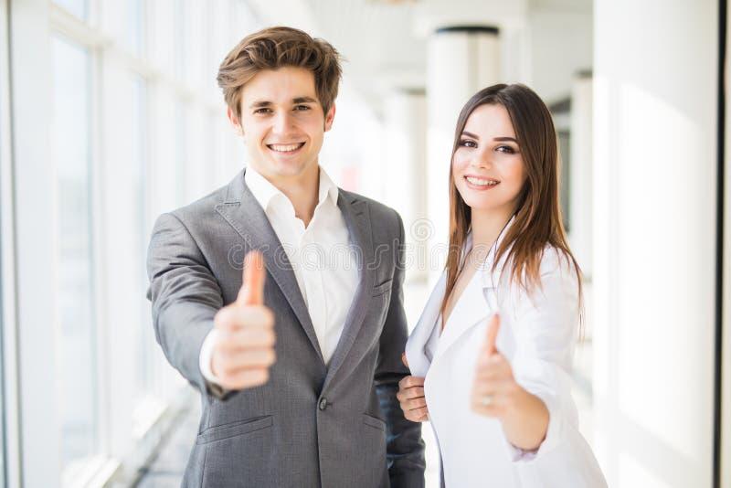 Bedrijfspaar die duimen in bedrijfsbureau tonen De bedrijfsvrouw en de bedrijfsman beduimelen omhoog stock fotografie