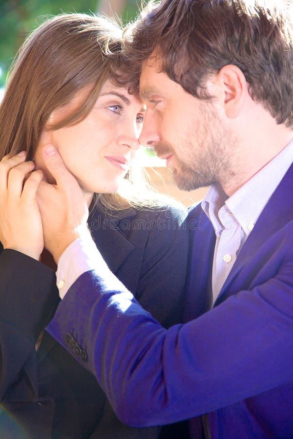 Bedrijfspaar die in liefde elkaar onderzoeken ogen royalty-vrije stock afbeelding