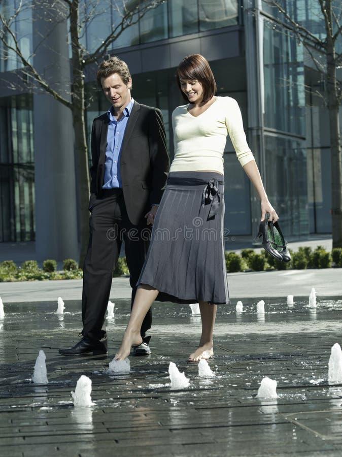 Bedrijfspaar die tussen Waterstralen lopen van Fontein royalty-vrije stock fotografie