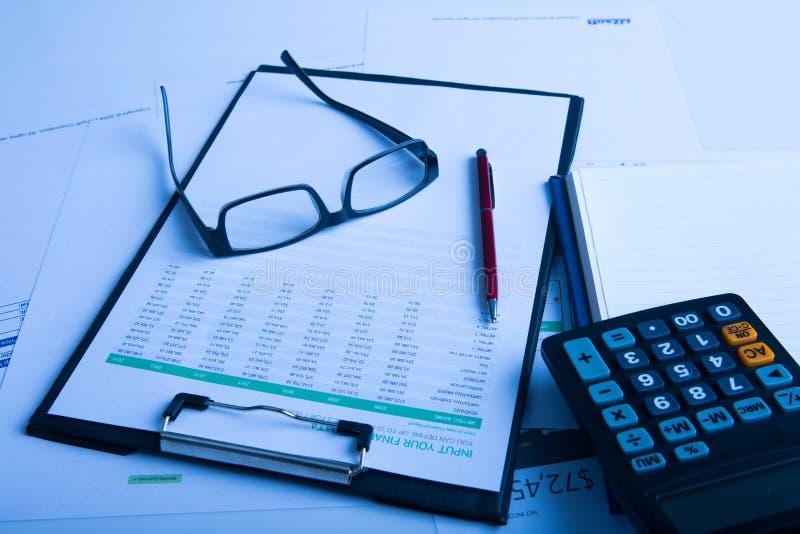 Bedrijfspen, calculator en glazen op financiële grafiek royalty-vrije stock afbeelding