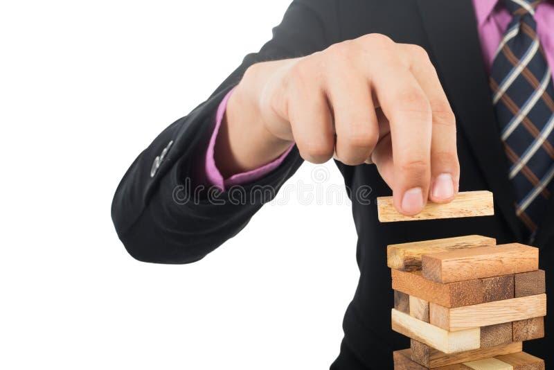 Bedrijfsrisicoconcept met houten jengaspel De zakenman leidt hallo royalty-vrije stock fotografie