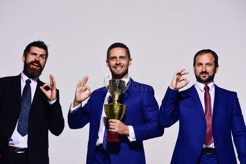 Bedrijfssucces en overwinningsconcept De bedrijfleiders houden gouden prijs stock foto's