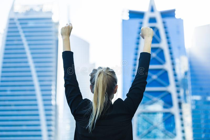 Bedrijfssucces - Vierende onderneemster die high-rises van het stadscentrum overzien royalty-vrije stock foto's