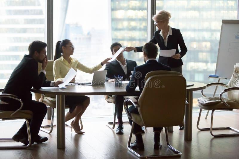 Bedrijfstafmedewerker die documenten geven die nieuw businessplan voorleggen aan team stock fotografie