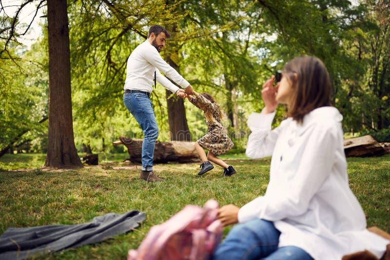 Bedrijfsvader die een dochter in park spinnen stock foto